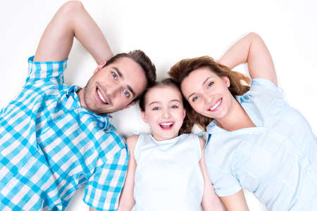 High angle portrait of caucasian happy smiling young family with two children lying down on white floor and looking at camera photo