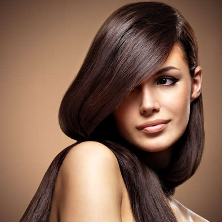 Beautiful young woman with long straight brown hair. Fashion model posing at studio over beige background Фото со стока