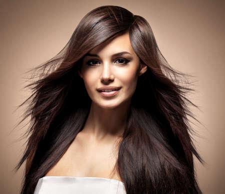 Modelka s dlouhými rovnými vlasy. Modelka představují ve studiu.