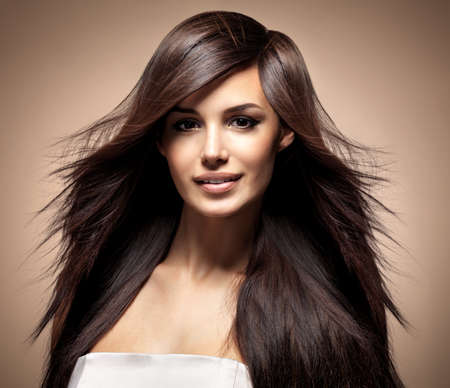 móda: Modelka s dlouhými rovnými vlasy. Modelka představují ve studiu.