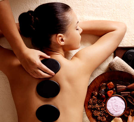 Young woman getting hot stone massage in spa salon. Beauty treatment concept.