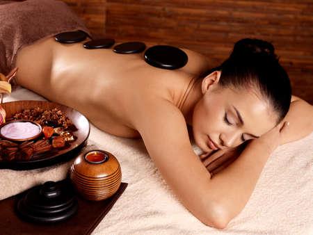 Jeune femme ayant massage aux pierres dans le spa salon. Style de vie sain.