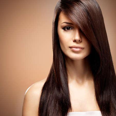 Joven y bella mujer con cabello castaño largo recto. Modelo de moda en estudio sobre fondo de color beige