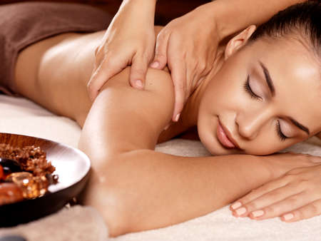 masseur: Masseur doing massage on woman body in the spa salon. Beauty treatment concept.