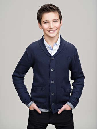 幸せかなり 10 代の少年は、ファッションモデルとしてスタジオでポーズします。