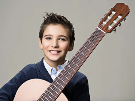 Smiling boy with guitar. Teenager boy with classic wooden acoustic  guitar