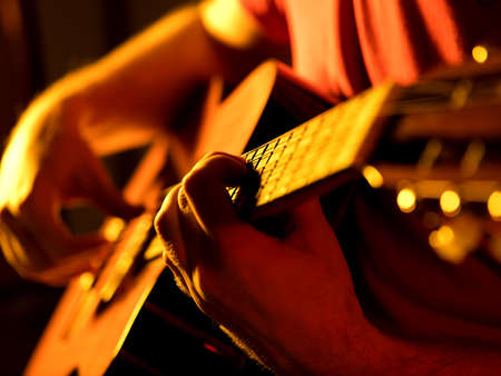 man playing classic guitar on a stage musical concert close-up view Stock Photo