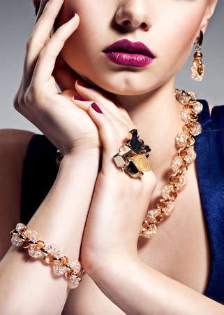 Part of female face with beautiful golden jewelry on body and bright make-up -  posing at studio