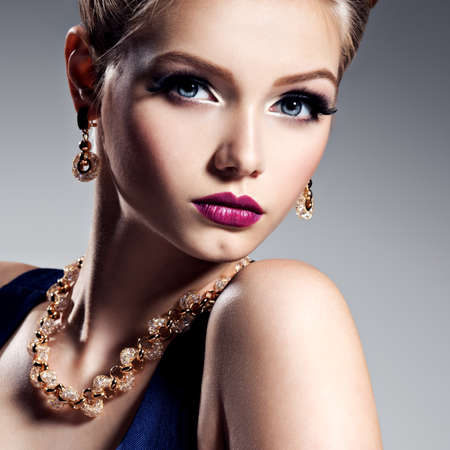 Pretty girl with beautiful gold jewelry and bright make-up -  posing at studio Stock Photo