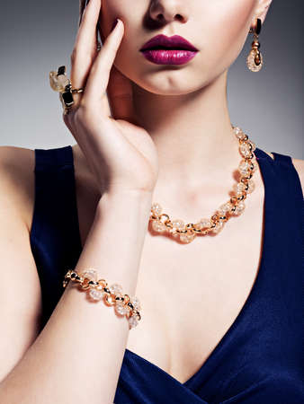 fashionable woman: Part of female face with beautiful golden jewelry on body and bright make-up -  posing at studio