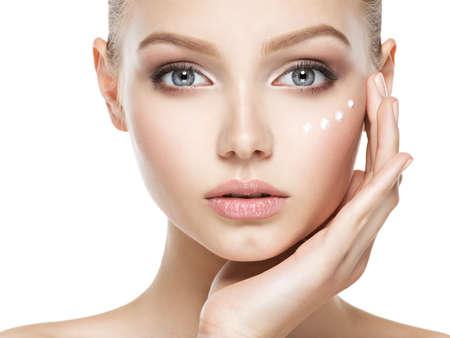 Junge Frau mit kosmetischer Sahne auf einem sauberen, frischen Gesicht Standard-Bild - 63393363