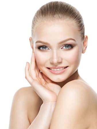 Krásná tvář mladé usmívající se žena s čistou čerstvou kůže - izolovaná na bílém
