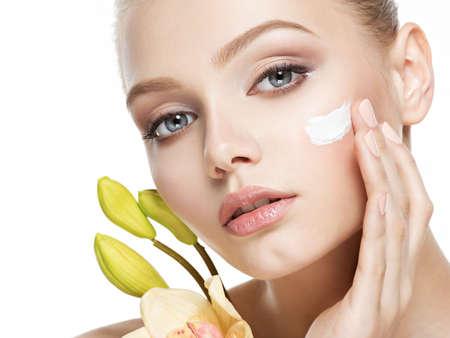 Junge Frau mit kosmetischer Sahne auf einem sauberen, frischen Gesicht
