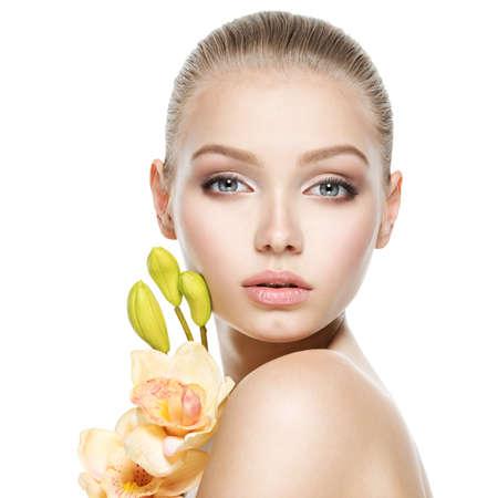Beau visage de la jeune femme en bonne santé avec des fleurs - isolé sur blanc