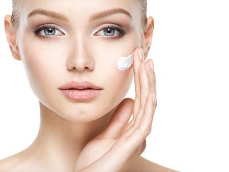Giovane donna con crema cosmetica su una faccia pulita fresca Archivio Fotografico - 63650649