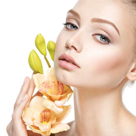 Cara hermosa de la mujer joven y sana con flores - aislados en blanco