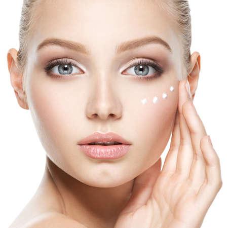 きれいな顔に化粧品クリームを持つ若い女性 写真素材