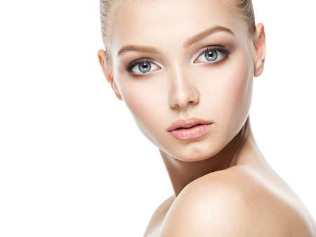 Beau visage de jeune femme caucasien avec la peau fraîche parfaite santé - isolé sur blanc. Concept de soins de la peau.
