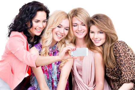 group shot: Young beautiful smiling women looking at the mobile phone - isolated on white background. Stock Photo