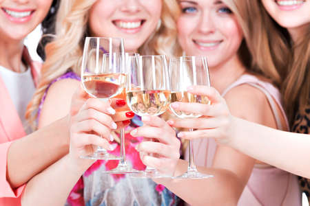 wine  pink: Closeup portrait of young happy women have party and drinking wine - isolated on white. Stock Photo