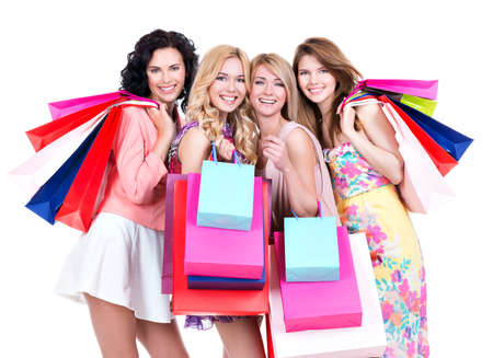 Portrait of beautiful smiling women with multicolor shopping bags standing on a white background. photo