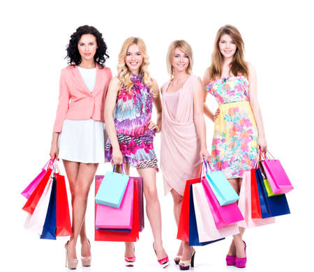 Beautiful happy women with multicolor shopping bags in full length isolated on a white background. photo