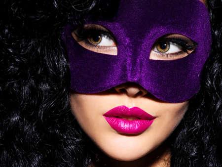 femme noire nue: Portrait d'une belle femme avec des cheveux noirs et un masque de théâtre violet sur le visage. ongles pourpres. Banque d'images