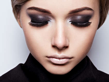 black: The girls face closeup with long black lashes. fashion makeup