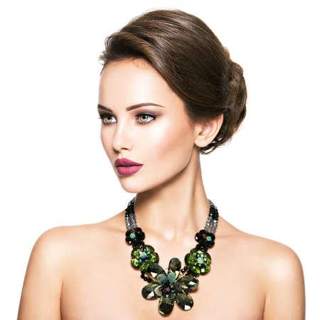 anochecer: Mujer hermosa con joyería de moda. Retrato de una chica muy de moda con collar de cristal verde. Presentación modelo estadounidense sobre el fondo blanco