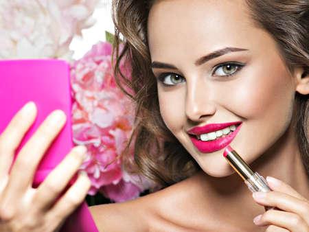 Smiling Woman applying lipstick. Beautiful girl makes makeup