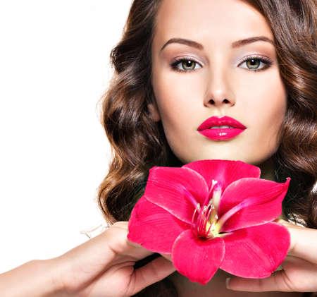 poses de modelos: Retrato de joven hermosa adulta joven con labios rojos brillantes y flores cerca de la cara - aislada sobre fondo blanco