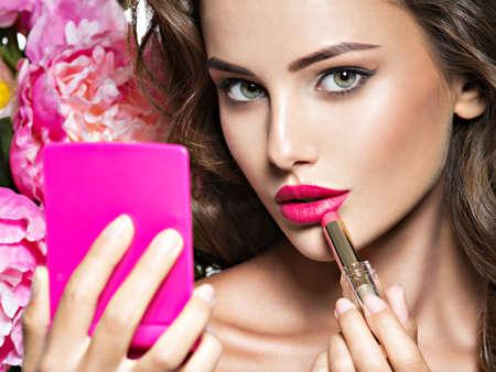 女性は、鏡を見て口紅を適用します。美しい少女は、メイクアップ