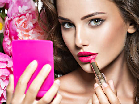 Woman applying lipstick looking at mirror. Beautiful girl makes makeup Foto de archivo