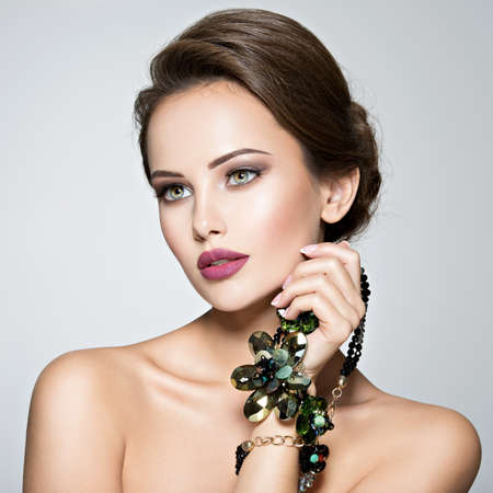 1: Beautiful woman with fashionable jewelry.  Portrait of a pretty fashion girl with green glass necklace. American Model posing at studio Stock Photo