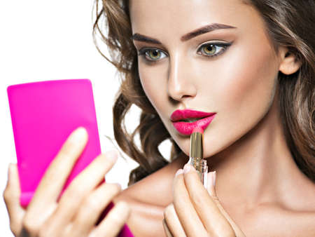 applying: Woman applying lipstick looking at mirror. Beautiful girl makes makeup Stock Photo
