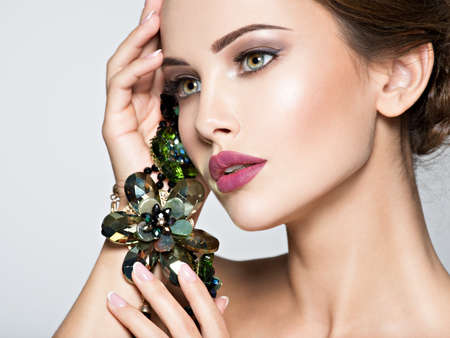 Mujer hermosa con joyería de moda. Retrato de una chica muy de moda con collar de cristal verde. Modelo estadounidense presenta en el estudio