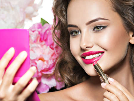 Smiling Woman applying lipstick looking at mirror. Beautiful girl makes makeup