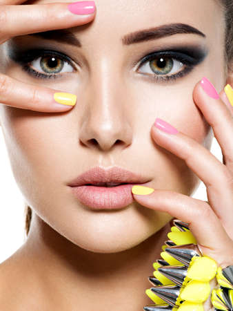 elegance fashion girls look sensuality young: Closeup face of beautiful woman with multicolored nails