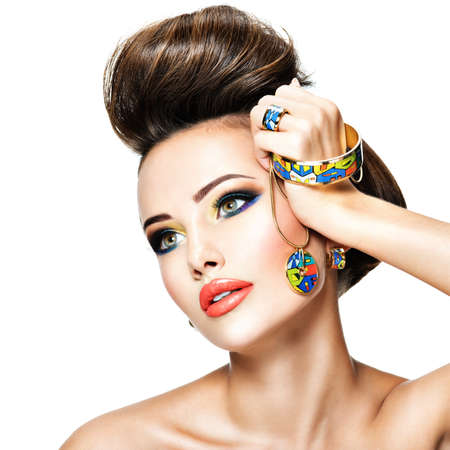 Fashion woman with beautiful art jewelry and creative hairstyle.  Portrait of a pretty  girl with modern necklace.
