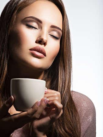 mujer tomando cafe: Mujer con la taza de café. hods niña de adultos hermosas en manos taza con la bebida caliente en el fondo blanco -