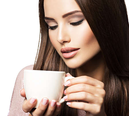 aroma: Woman with cup of coffee. Beautiful adult girl hods in hands mug with hot drink - on white background