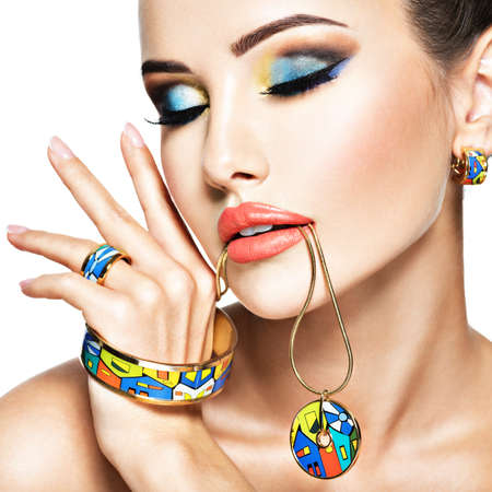 Beautiful woman with creative bright colored make-up. Fashion girl with glamour jewelry Stock Photo