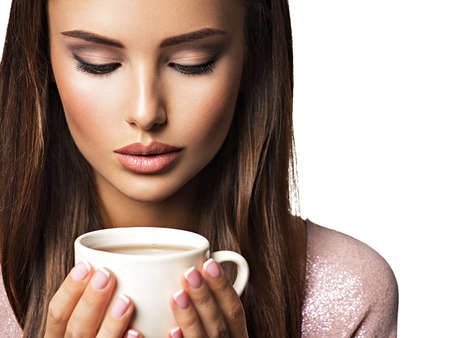 beautiful background: Woman with cup of coffee. Beautiful adult girl hods in hands mug with hot drink - on white background