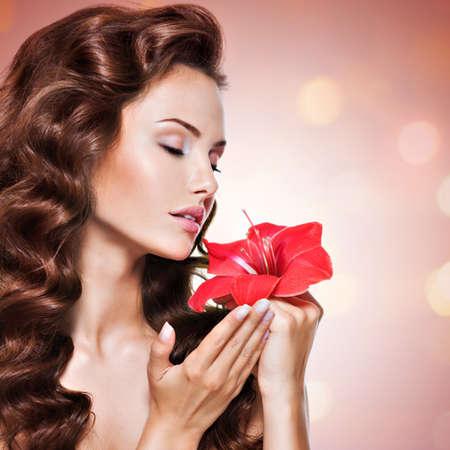 poses de modelos: Retrato de joven y bella mujer con olor a flor cerca de la cara - fondo brillante. Foto de archivo