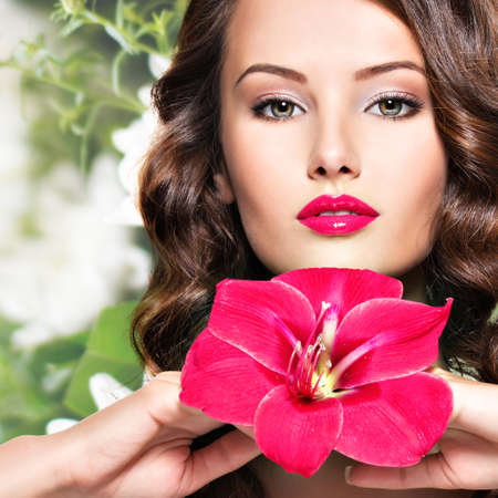 1: Portrait of young beautiful adult girl with bright red lips and flower near the face - creative background.