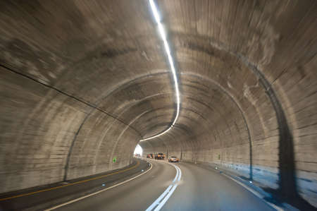 curve road: Interior of an urban tunnel with cars far afield.
