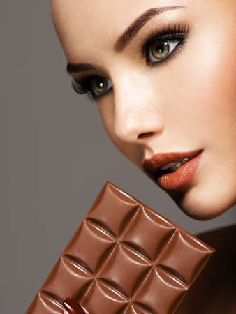 Portrait of glamour beautiful woman with brown makeup  holds  chocolate