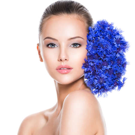 Face of a beautiful girl  with blue posy fild flowers. Skin care concept.