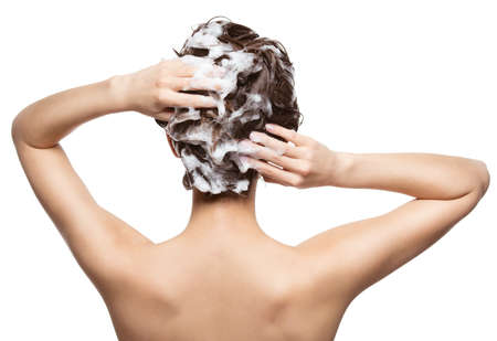 Woman soaping the hair. Beauty treatment - isolated on white background LANG_EVOIMAGES