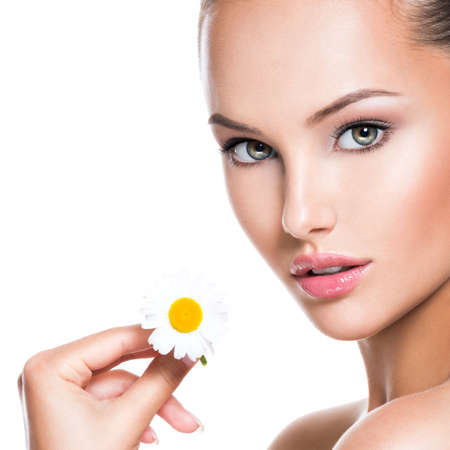 Closeup face of young beautiful woman with singl camomile in hand.  Isolated on white background LANG_EVOIMAGES
